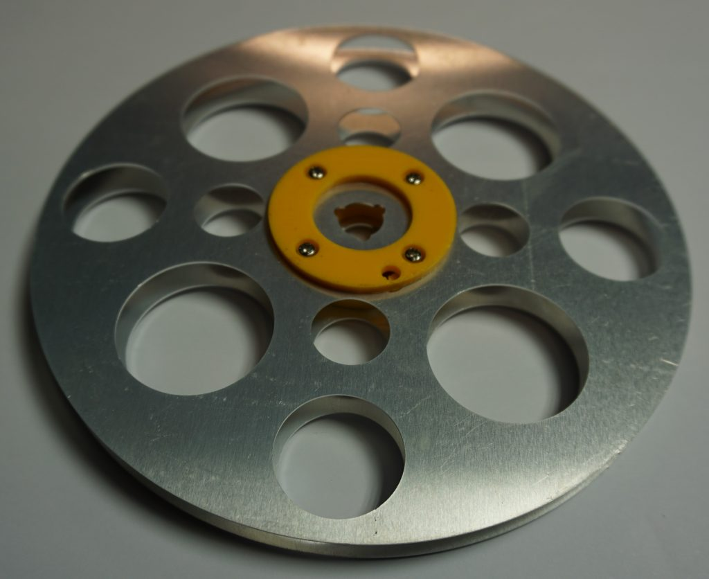 Super 8 film reel side view with laser cut cluminium sides and 3d printed ABS plastic hub